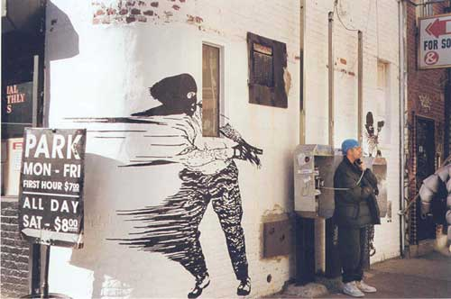 Man on pay phone with a fleeing gangster painted on wall