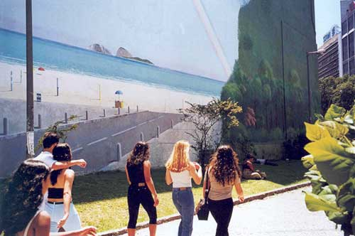 People walking in front of a wall painted with a beach scene